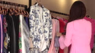 Clothing store owner helping customer with choosing dress