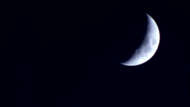 Cloud creeping over crescent moon Available in HD.