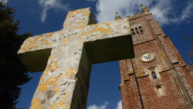 T/L cloud shadows passing over lichen-covered cross and church tower, UK