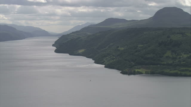 Clouds and silhouetted mountains frame Loch Ness. Available in HD.