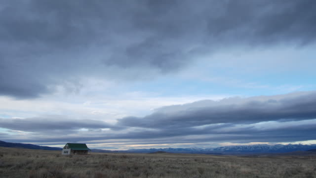 Clouds billow over house on prairie.