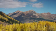 WS TD Clouds blowing over rocky mountains with changing aspen trees in valley during autumn / Marble City, Colorado, United States