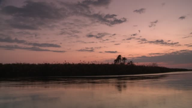 Clouds drift over a river at sunset. Available in HD.