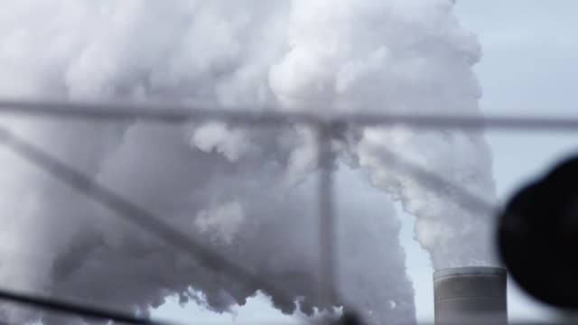 Clouds from smokestacks in daylight