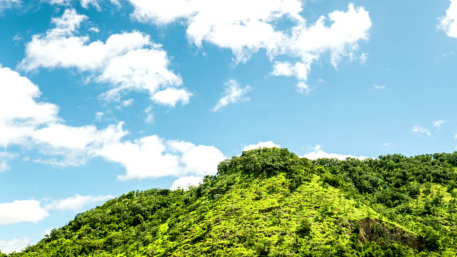 Clouds motion passing over green tropical mountain