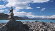 T/L, WS, Clouds over Lake Tekapo and mountains, stack of rocks in foreground, South Island, New Zealand
