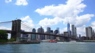 Clouds over the Brooklyn Bridge and Manhattan Skyscrapers. Ferry boat runs on the East River.