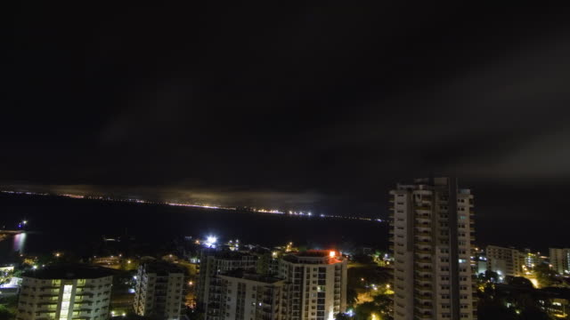 WS ZI T/L Clouds passing over high rise building at night / Darwin, Northern Territory, Australia.