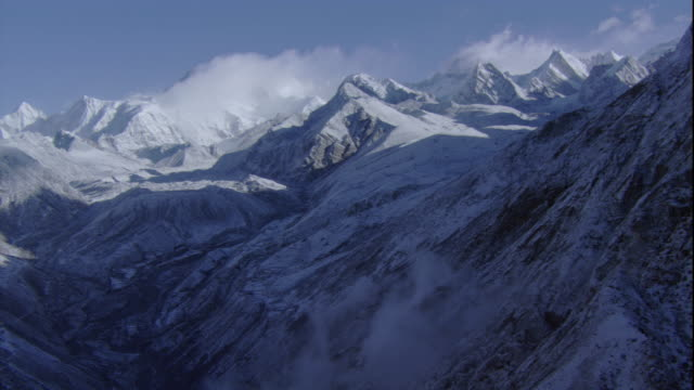 Clouds rest on snowy mountain peaks in the Himalayas. Available in HD.