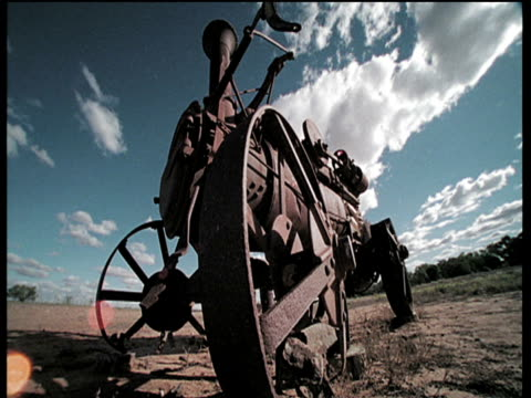 Clouds scud in blue sky over rusty old traction engine