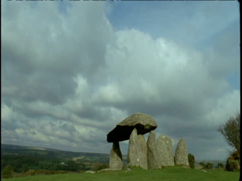 Clouds scud over ancient Pentre Ifan dolmen as crowd admires it