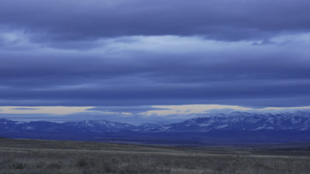 Clouds scud over plains and mountains as night falls.