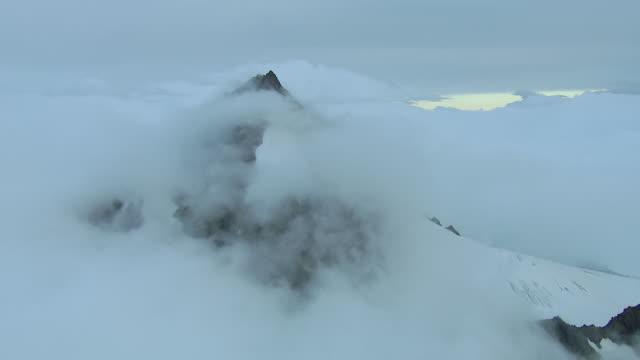 Clouds Surround Snow Covered Peak