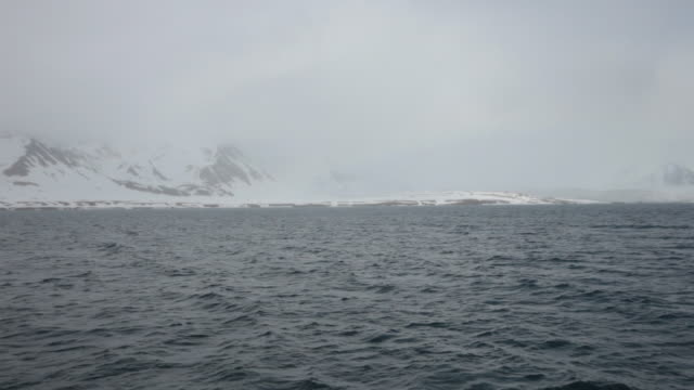 Cloudy and stormy weather at Isfjorden, the second longest fjord in the Norwegian archipelago of Svalbard; mountains covered by snow