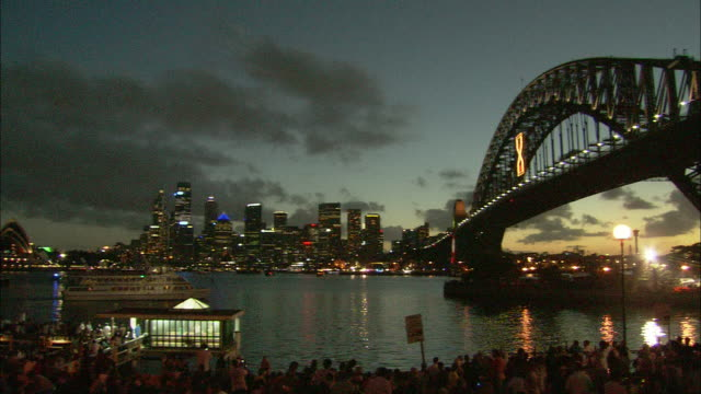 A cloudy sky glows at sunset behind Sydney Harbour Bridge near a New Year's Eve crowd.