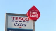 A 'Clubcard Fuel Save' sits on a sign at the petrol station outside a Tesco Extra supermarket store operated by Tesco Plc in Basildon UK on Wednesday...