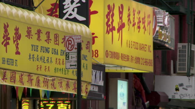 A cluster of restaurant signs in Chinatown on a grey day.