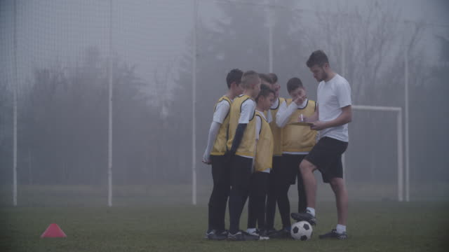 4K: Coach Giving Instruction To His Kids Soccer Team.