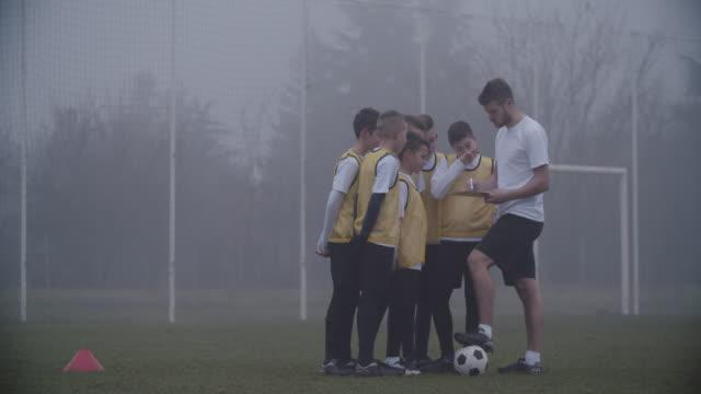 4K: Coach ger instruktion till hans barn fotbollslag.