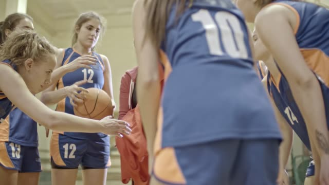 Coach giving uniform to female basketball players