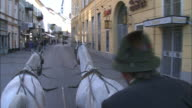 Coachman drives horse-drawn carriage round streets of Bad Ischl, Austria
