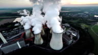 AERIAL: Coal fired power station with cooling towers releasing steam into atmosphere