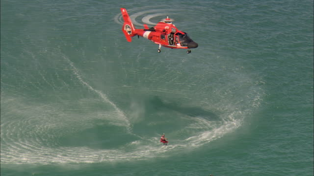 LOW AERIAL U.S. Coast Guard helicopter hovering over water during training exercise, man saving swimmer in sea, near Marathon Key, Florida, USA