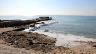 Coastline shares pier, land and wavy sea in winter