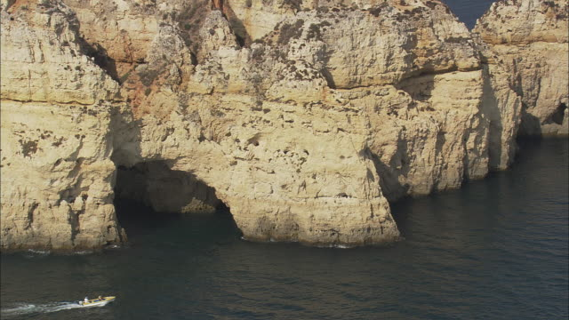 AERIAL WS Coastline with sea stacks and motorboat moving by / Lagos, Faro, Portugal