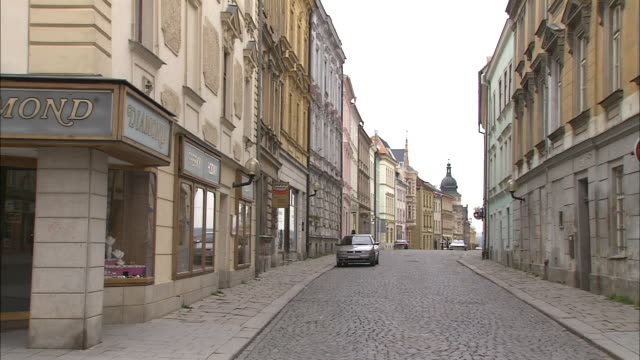 Cobbled street with historic building facades and Church tower at end