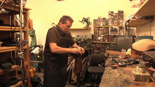 MS Cobbler attaching new heel to customer's boot in his shop / Lebanon, New Hampshire, USA
