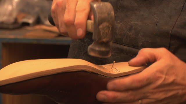 CU ZI TU TD SLO MO Cobbler attaching new sole with hammer and nails as he repairs and reconditions customer's boot in his shop / Lebanon, New Hampshire, USA