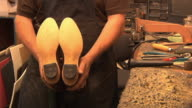 CU ZO SLO MO Cobbler displays his repair and reconditioning work after he finished attaching the new sole, heel and heel pad to customer's boots in his shop / Lebanon, New Hampshire, USA