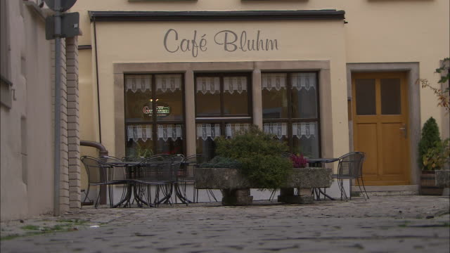 A cobblestone alley leads to a quaint cafe in Frankfurt, Germany.