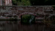 A cobblestone bridge stretches across the moat at Harvington Hall in Kidderminster, England. Available in HD.
