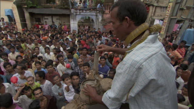 A cobra strikes at a snake charmer in front of a large crowd of onlookers. Available in HD.