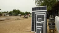 A CocaCola Co advertisement sits roadside in N'Djamena Chad on Tuesday Aug 15 Solar panels sit for sale from a roadside household store