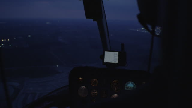 cockpit of helicopter, aerial night filming over city