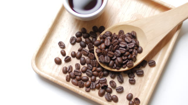 Coffee Beans and Hot Black coffee on Wooden dish on white table background , dolly shot right to left
