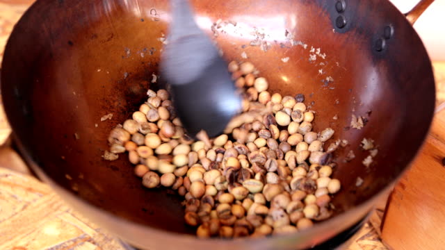 Coffee beans are roasting in pan. Traditional techniques