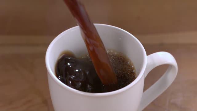 CU SLO MO Coffee being poured into white mug on wooden table / New Jersey, USA