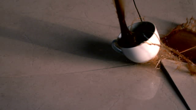 Coffee cup smashing onto surface and cracking it
