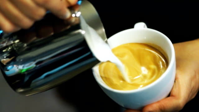 Coffee latte art, Milk pouring by a Barista.