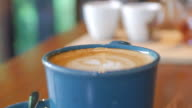 Coffee latte art on Blue cup and wooden Table , Dolly Shot