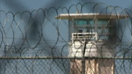 Coils of razor wire on top of fencing w/ top of prison guard tower BG Maximum security incarceration not jail correctional facility the farm