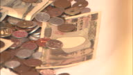 Coins and bills fill an offering plate.