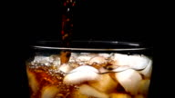 Pouring cola soda into glass of ice with splashes at slow motion on black background