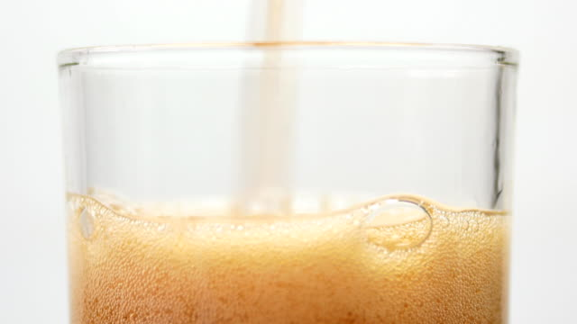 cola splashing in drinking glass
