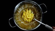colander spoonful of Penne pasta splashing into boiling pot - Top Shot