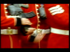 Cold stream Guards' torsos as they march and raise hands to hold rifles